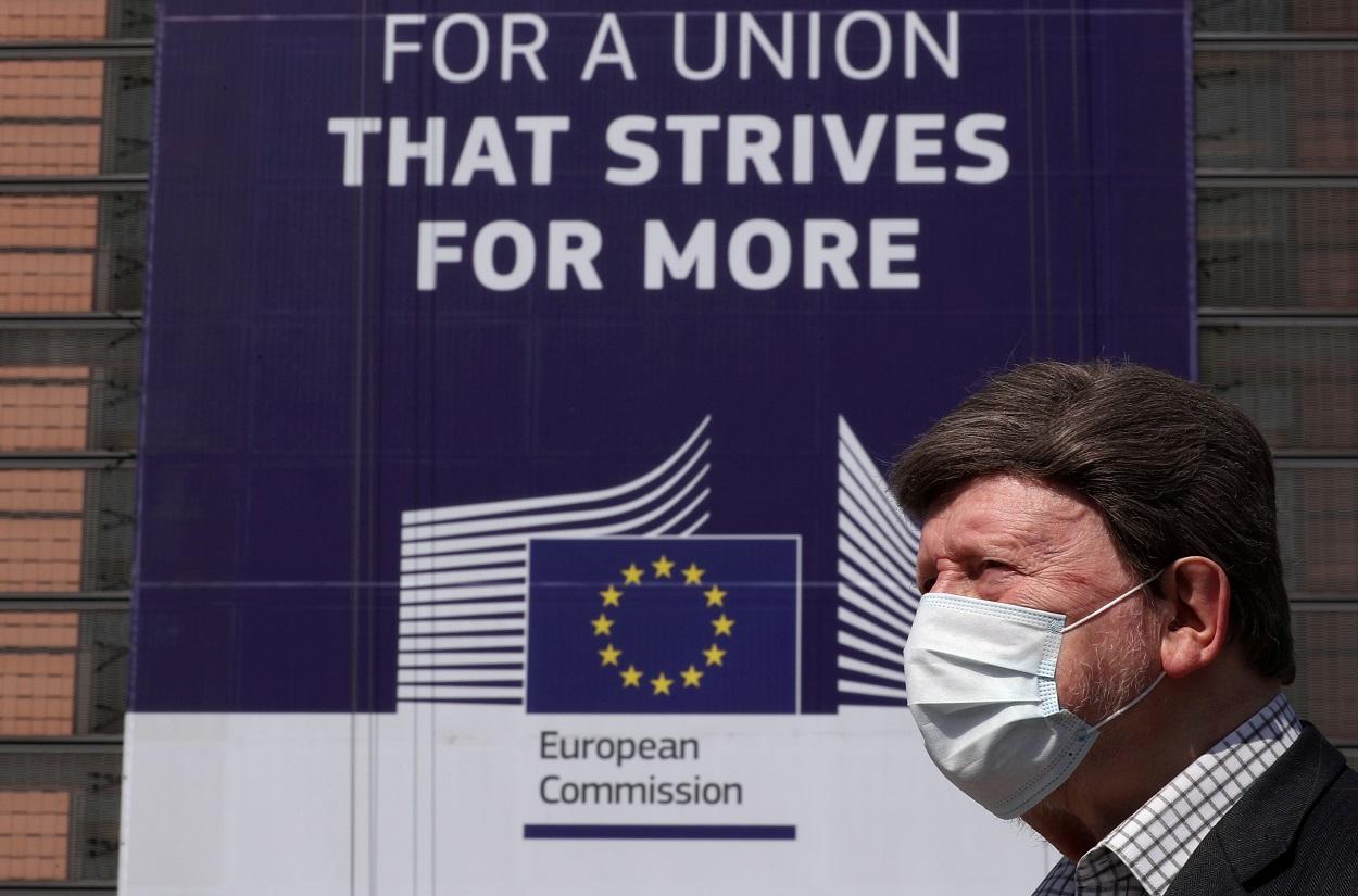 """Un hombre con mascarilla para por delante de la sede de la Comisión Europea en Bruselas, donde cuelga un cartel con el lema """"Por una Unión que se esfuerza por lograr más"""". REUTERS/Yves Herman"""