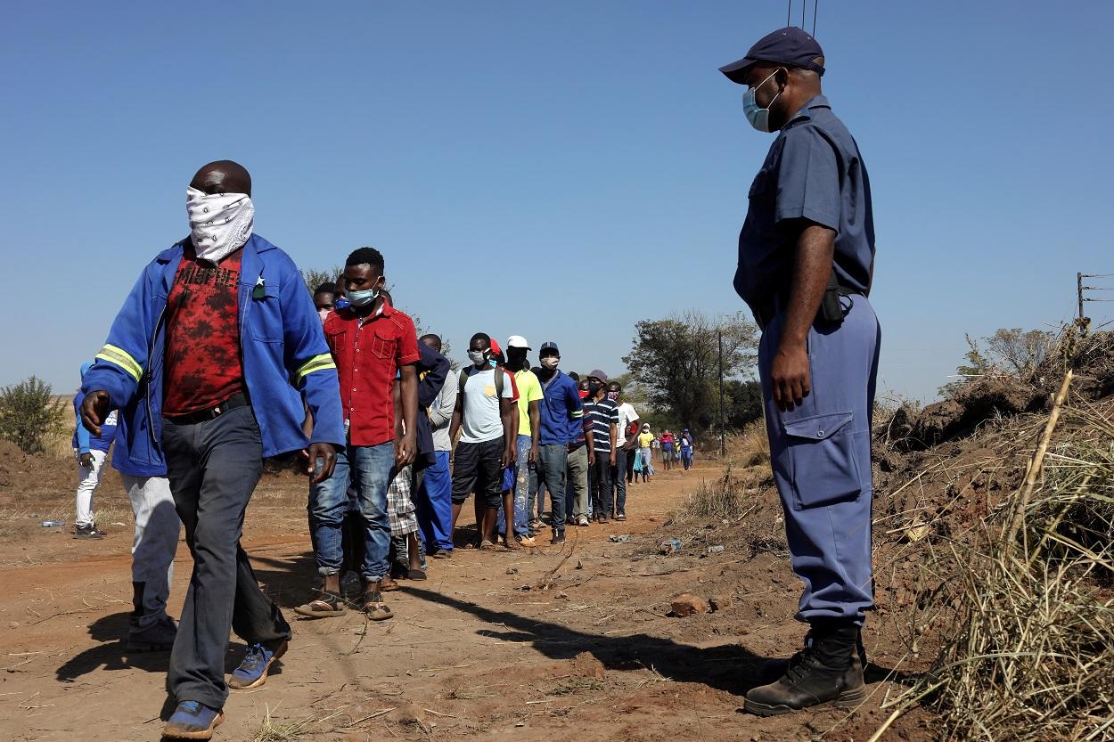 Una cola de personas con mascarillas para recibir ayuda alimentaria en el asentamiento informal de Itireleng, cerca del suburbio de Laudium en Pretoria, Sudáfrica. REUTERS / Siphiwe Sibeko