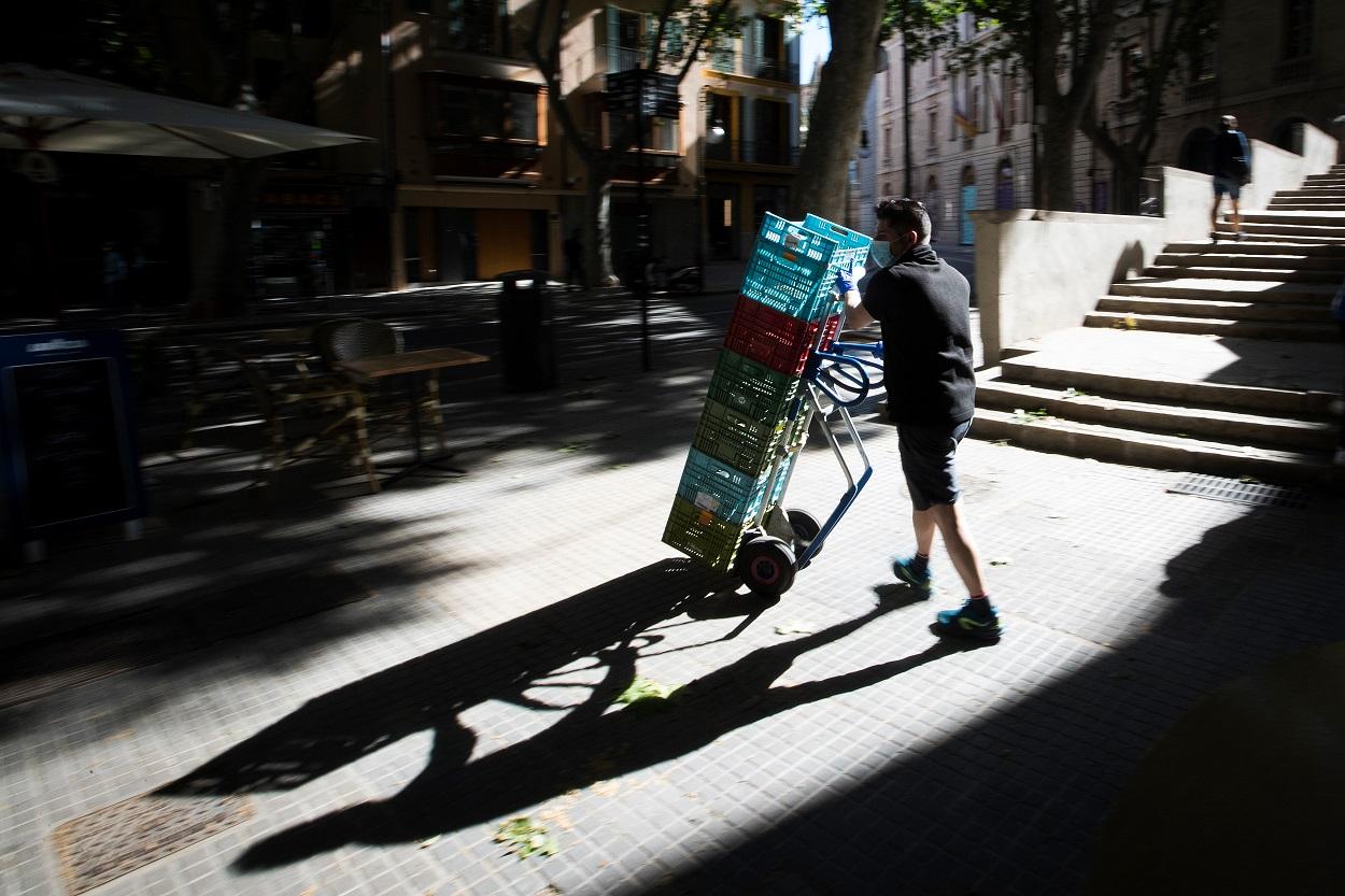 Un trabajador acarrea unas cajas por el centro del Palma de Mallorca. AFP/JAIME REINA