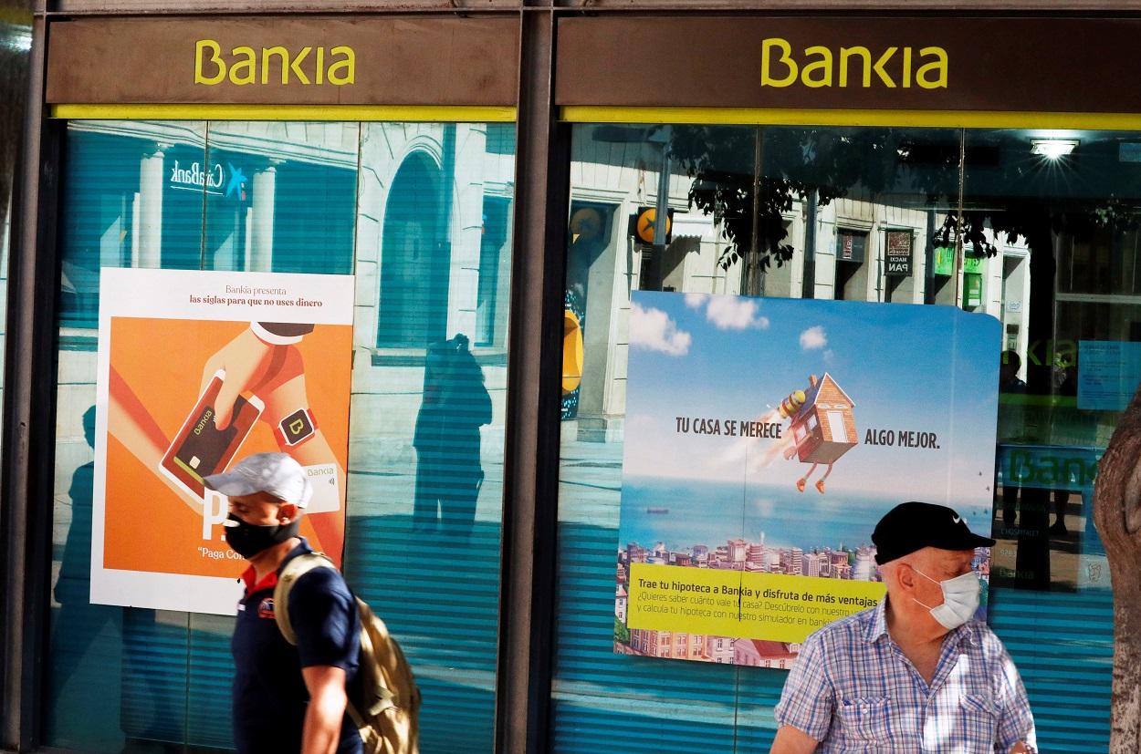 Una oficina de Bankia en Barcelona, en cuyas ventanas se refleja una sucursal cercana de Caixabank. REUTERS/ Albert Gea