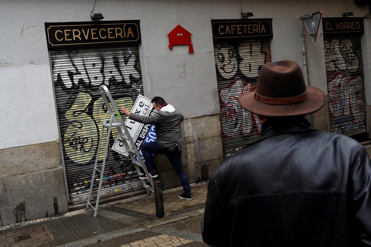 Un hombre se prepara para colgar el cartel de 'Disponible' en el local de una cafetería cerrada durante la pandemia del coronavirus, en el centro de Madrid. REUTERS/Susana Vera