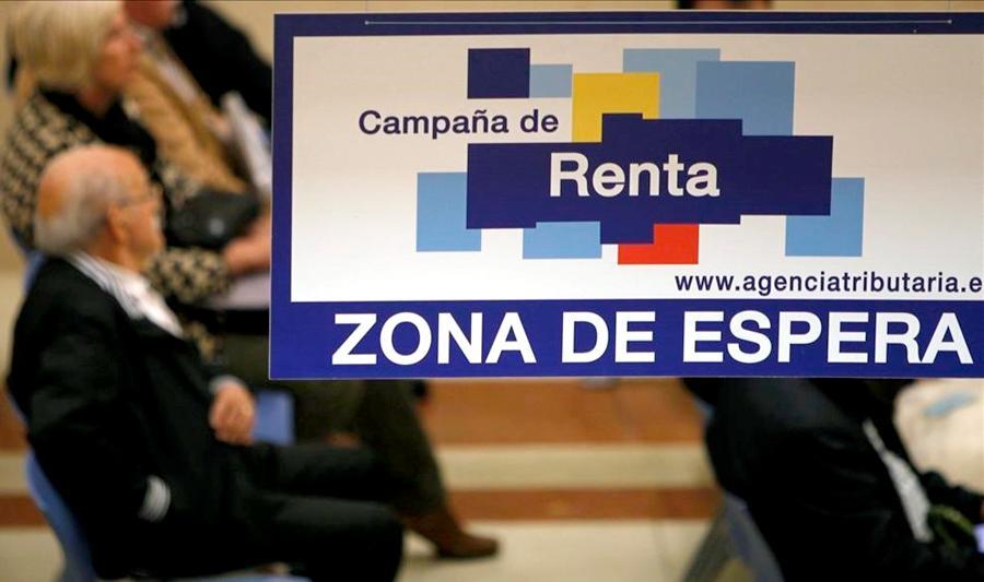 Contribuyentes esperan a ser atendidos en una oficina de la Agencia Tributaria durante la Campaña de la Renta. EFE