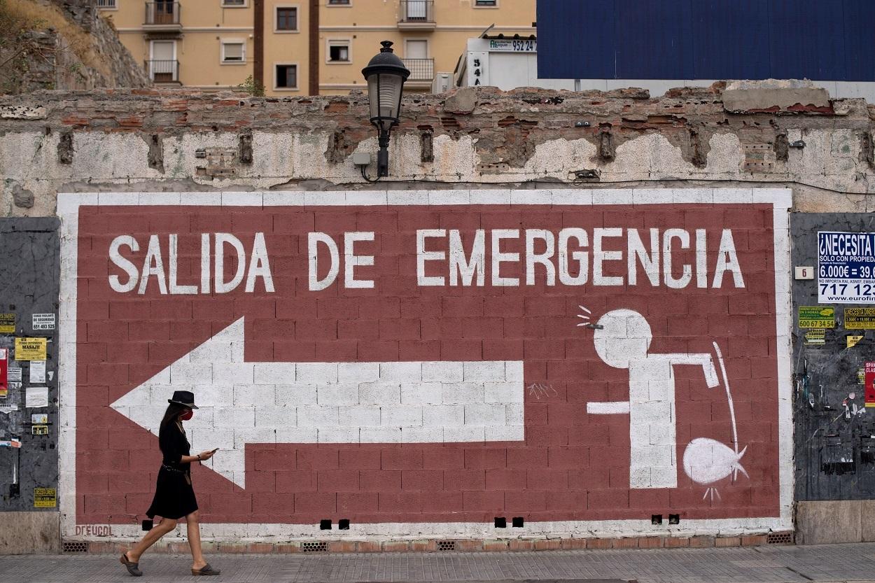 Una mujer con mascarilla pasa delante de una pintada en Malaga. AFP/JORGE GUERRERO