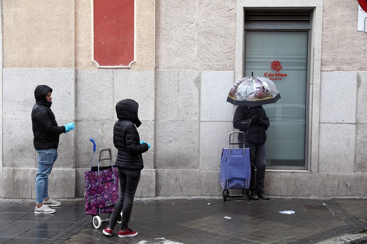 Varias personas guardan cola, manteniendo la distancia de seguridad, junto a un centro de Cáritas en Madrid. REUTERS/Sergio Perez