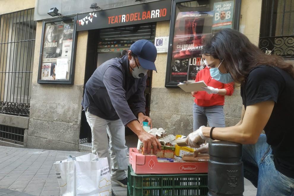 Voluntarios repartiendo alimentos en la puerta del Teatro del Barrio, de Madrid. Foto: Guillermo Martínez
