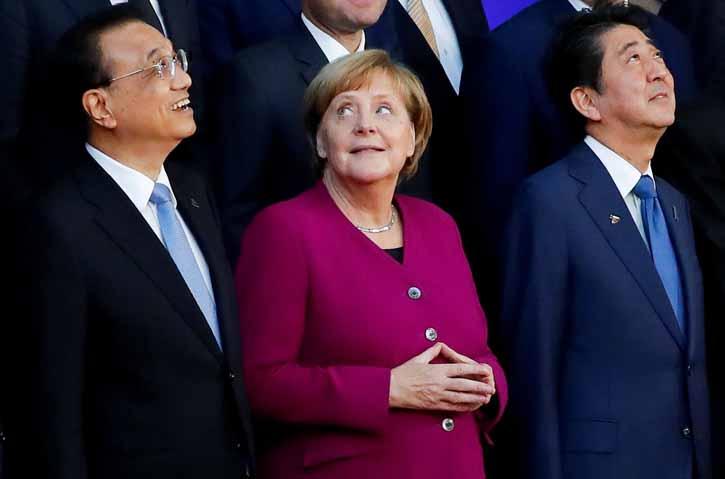 La canciller alemana Angela mwerkel, entre el primer ministro chino Li Keqiang y su homólogo japonés Shinzo Abe, en la foto de familia de la Reunión Asia-Europa, celebrada los días 18 y 19 de octubre en Bruselas. REUTERS/Yves Herman