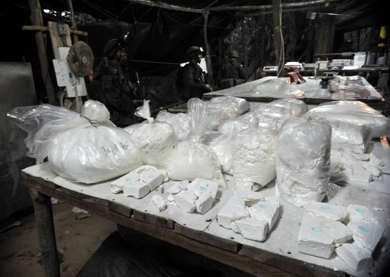 Policías colombianos colombian la droga aprehendida en un laboratorio ilegal de coaina, en la localidad de Puerto Gaitan (en el departamento de Meta), en octubre de 2011. AFP/Guillermo Legaria