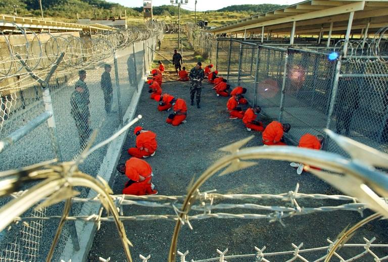 Foto de enero de 2002 de prisioneros taliban y de Al-Qaeda, vestidos con monos naranja, en la prisión de la base estadounidense de Guantanamo (Cuba). AFP