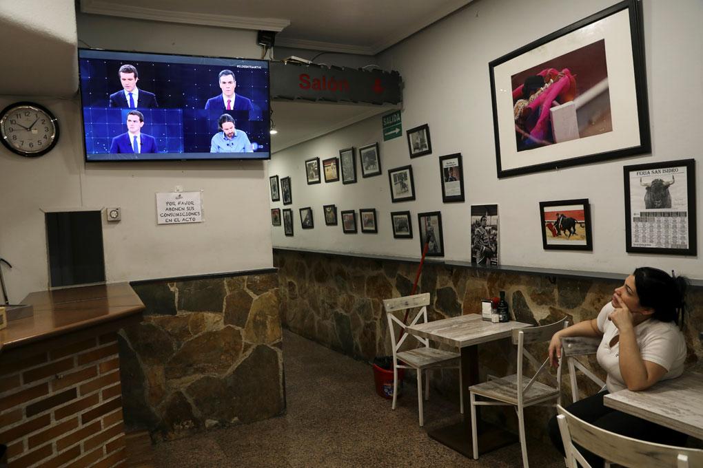 Una mujer observa el debate electoral a cuatro en TVE, en un televisión en un bar en Madrid. REUTERS/Susana Vera