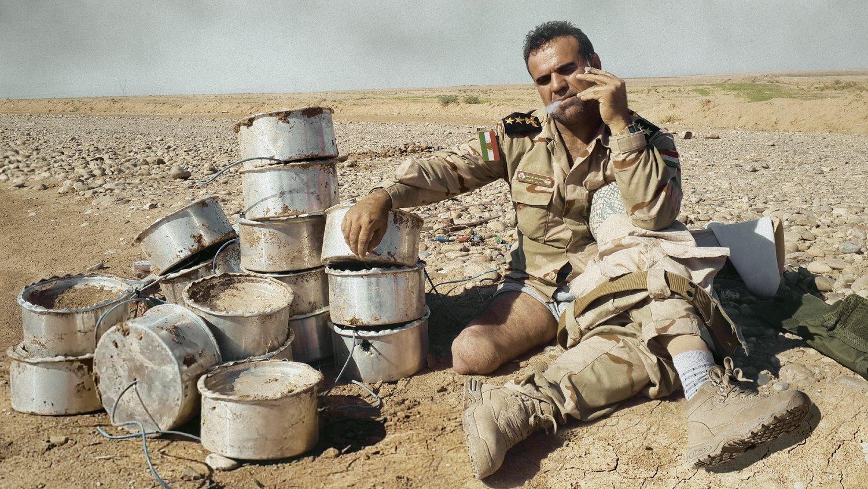 El coronel Fakhir Berwari se toma un descanso al lado de un montón de minas terrestres desactivadas.