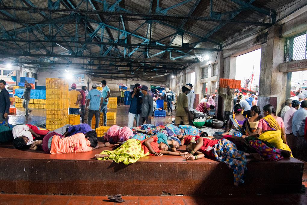 Las trabajadoras pesqueras migrantes descansan en el puerto de Mangalore