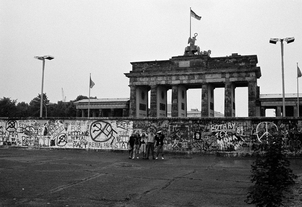 Foto de archivo de un grupo de turistas posa junto al Muro de Berlín, cerca de la Puerta de Brandenburgo, en junio de 1989. REUTERS/Fabrizio Bensch