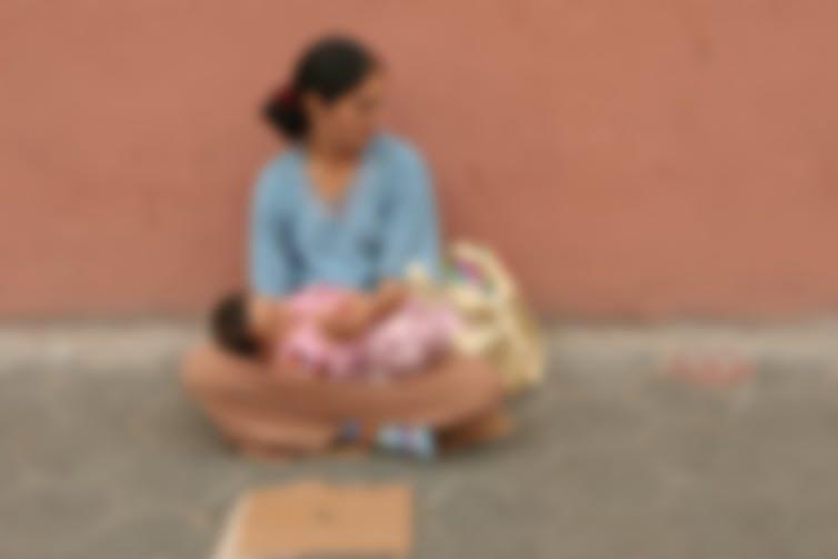 Una mujer con un bebé en el regazo en una calle de Barcelona en 2005. Se ha aplicado un filtro borroso para preservar sus identidades. Michael von Aichberger / Shutterstock
