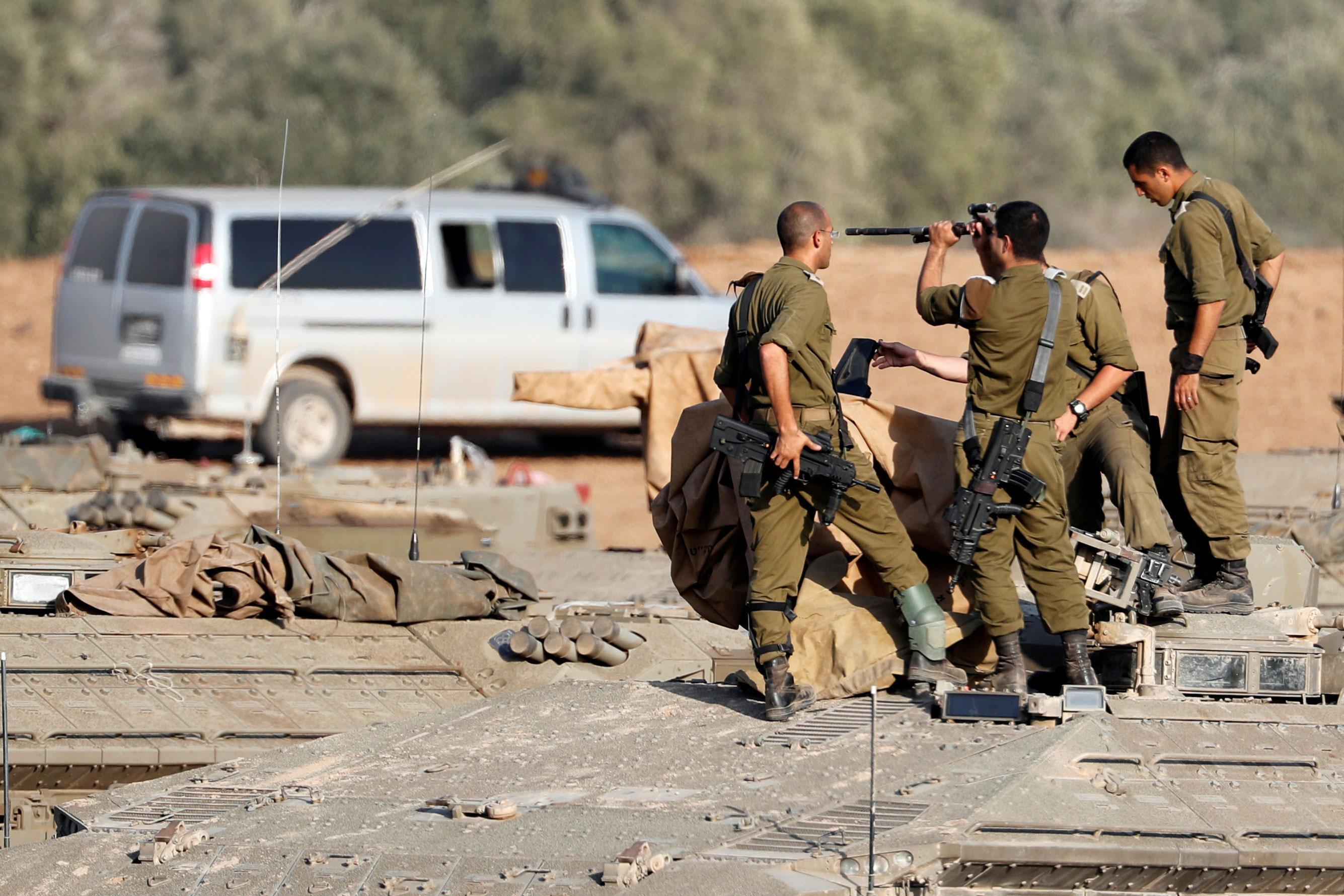 Los soldados israelíes revisan sus armas encima de un vehículo blindado de transporte de personal cerca de la frontera con Gaza, en el sur de Israel. REUTERS / Ronen Zvulun