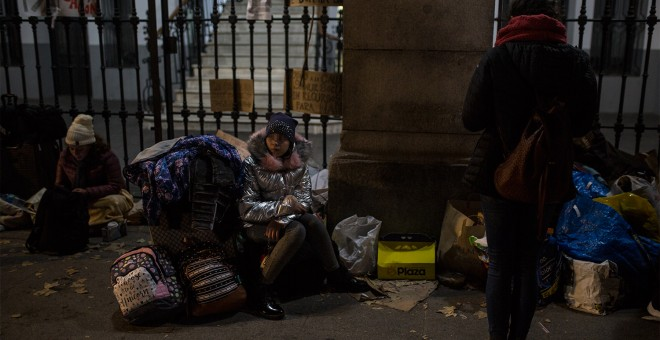 Una niña espera sentada sobre sus maletas a que los trabajadores del Samur Social de Madrid confirme si su familia, procedente de Georgia, tendrá plaza en un albergue para pasar la noche mientras formalizan su solicitud de protección internacional.- JAIRO VARGAS