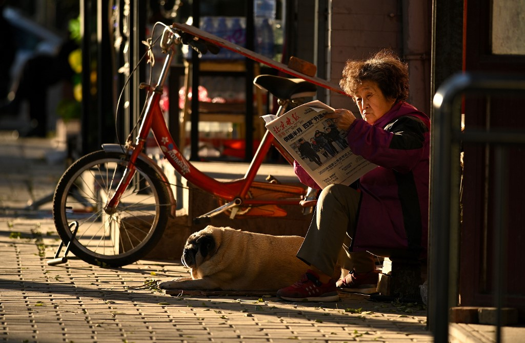 Una mujer lee el periódico en una calle de Pekín. AFP/Noel Celis