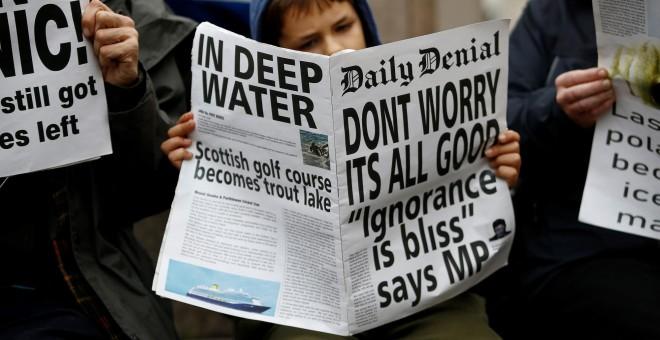 """Un manifestante lee un periódico falso con el titular: """"No se preocupe, todo va bien. Ignorancia es felicidad"""". REUTERS/Henry Nicholls"""