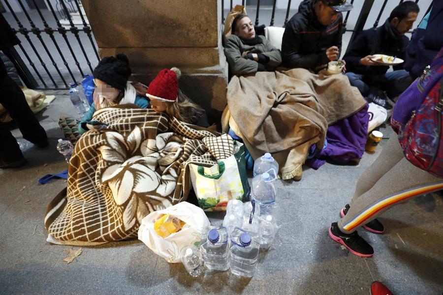 Solicitantes de asilo que esperan un recurso de acogida frente a las puertas del Samur Social de Madrid. EFE/Javier Lizón