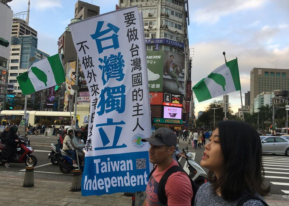 Varias personas pasan junto a una bandera en apoyo de la independencia de Taiwán, en el distrito comercial Ximending en Taipei. REUTERS / Ben Blanchard