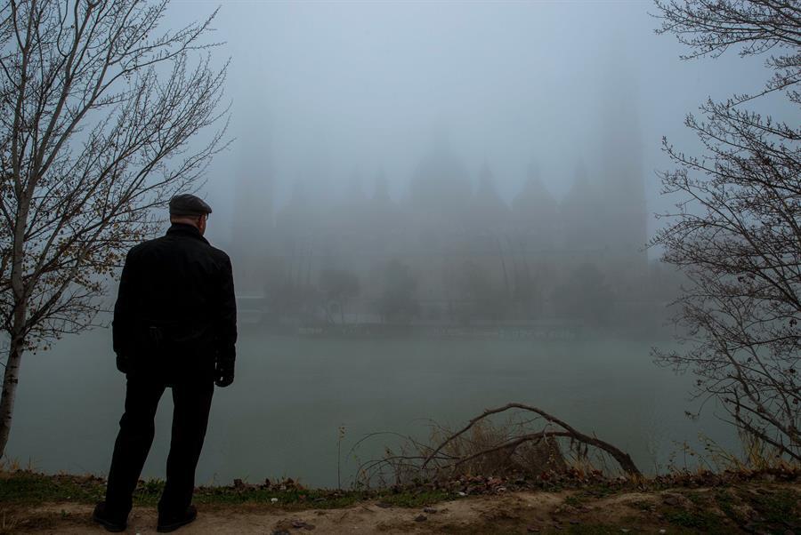 Un paseante contempla la silueta de la Basílica del Pilar cubierta por la niebla, en Zaragoza. EFE/Javier Cebollada