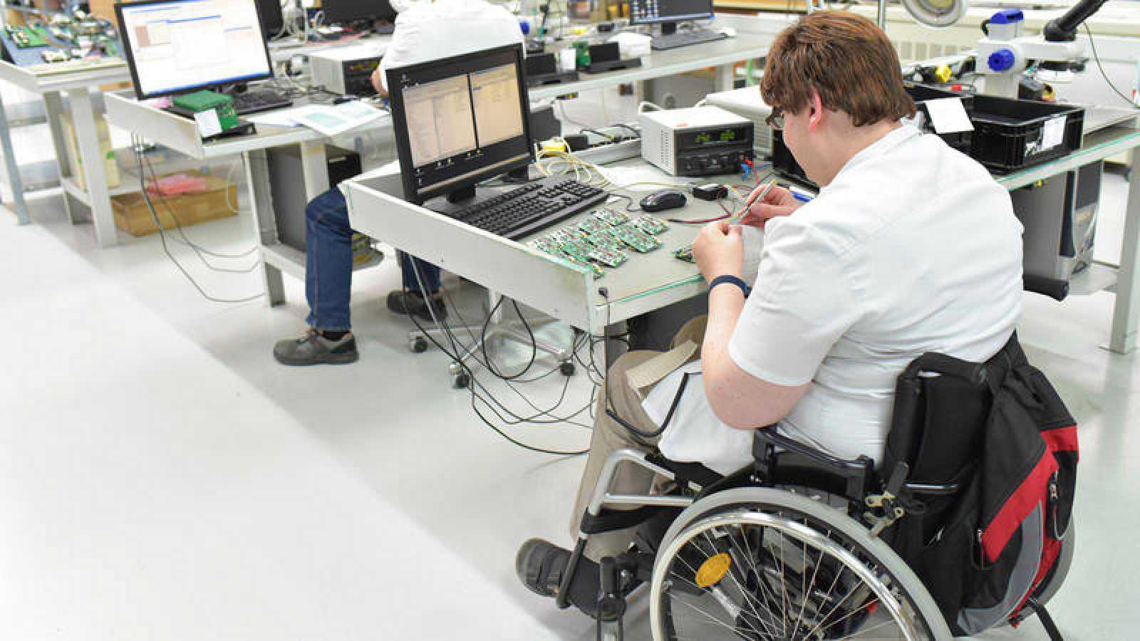 Discapacitado trabajando en una fábrica de ensamblaje de componentes electrónicos.