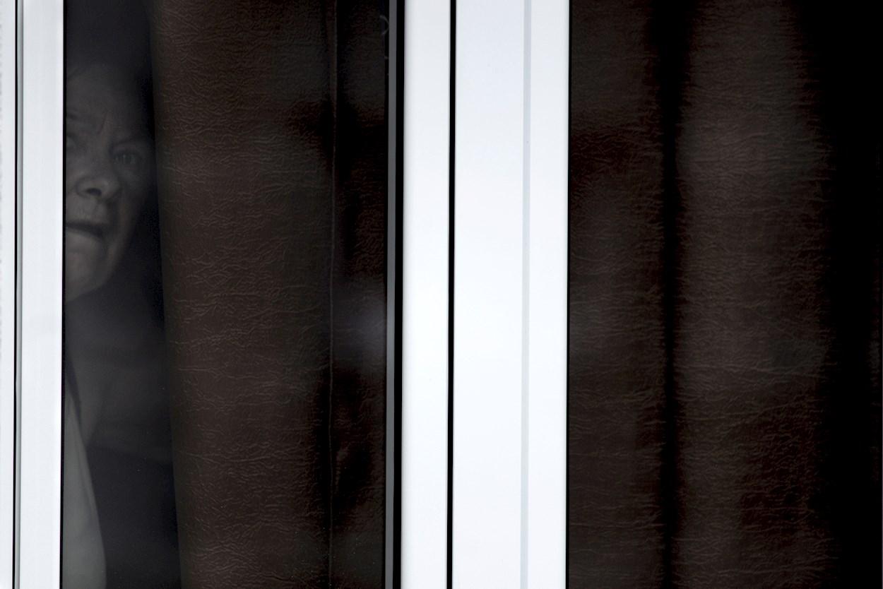 Una vecina se asoma a la ventana de su casa en el pueblo de Lamas (Xinzo de Limia), en Ourense. EFE/Brais Lorenzo