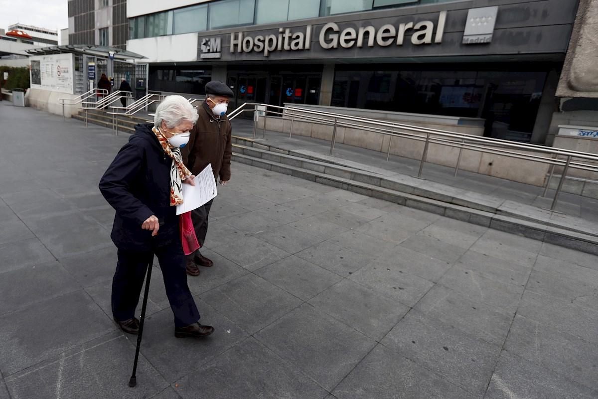 Una pareja de ancianos pasa ante el Hospital de La Paz, en Madrid. EFE/Mariscal