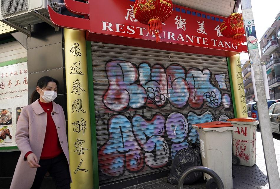 Una mujer con mascarilla pasa junto a un restaurante chino cerrado, en el barrio madrileño de Usera. REUTERS/Juan Medina