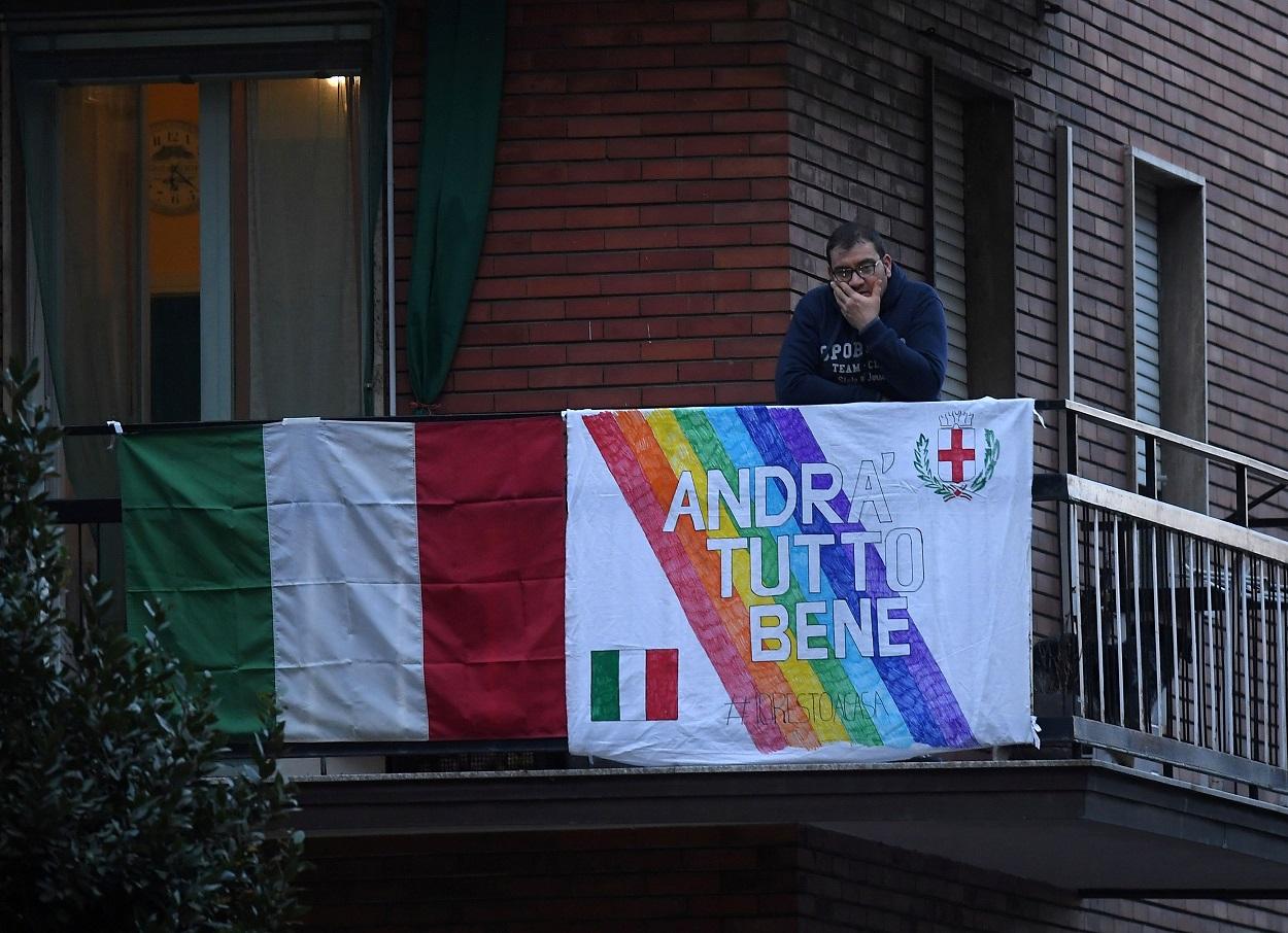 """Un hombre, en el balcón de su vivienda en Roma, con una pancarta con el lema """" Andra Tutto Bene"""" (""""Todo va a ir bien""""). REUTERS/Daniele Mascolo"""