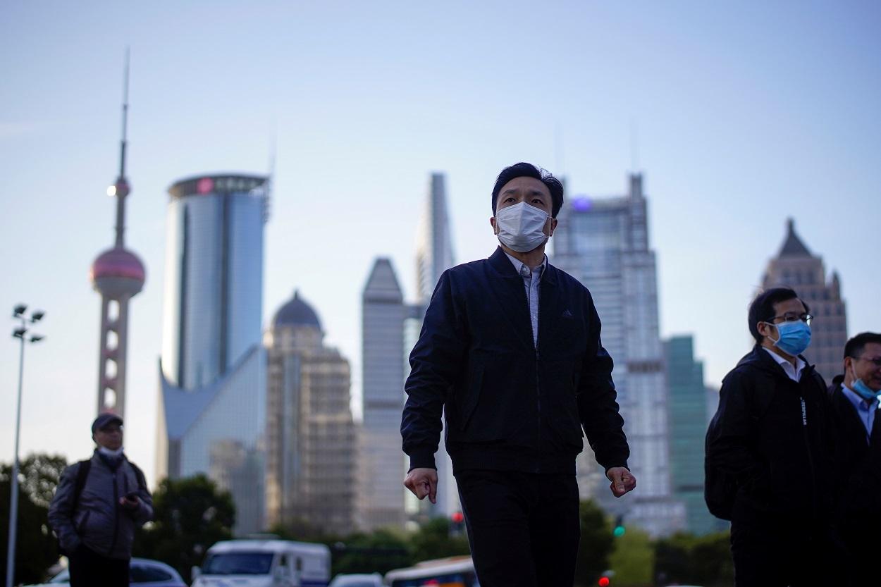 Personas con mascarillas en el distrito financiero de Shanghai. REUTERS/Aly Song