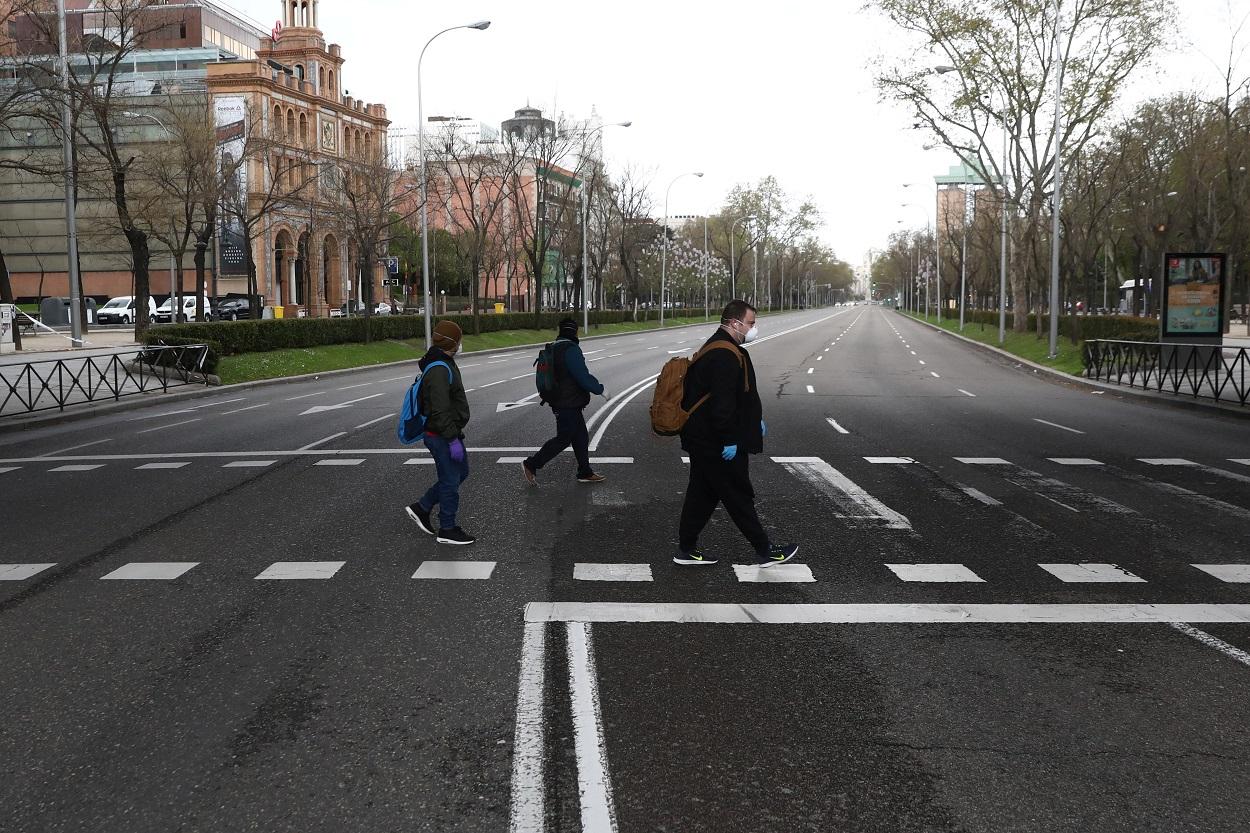 Tres personal con mascarilla cruzan el madrileño Paseo de la Castellana, con las calles prácticamente desérticas. REUTERS/Sergio Perez