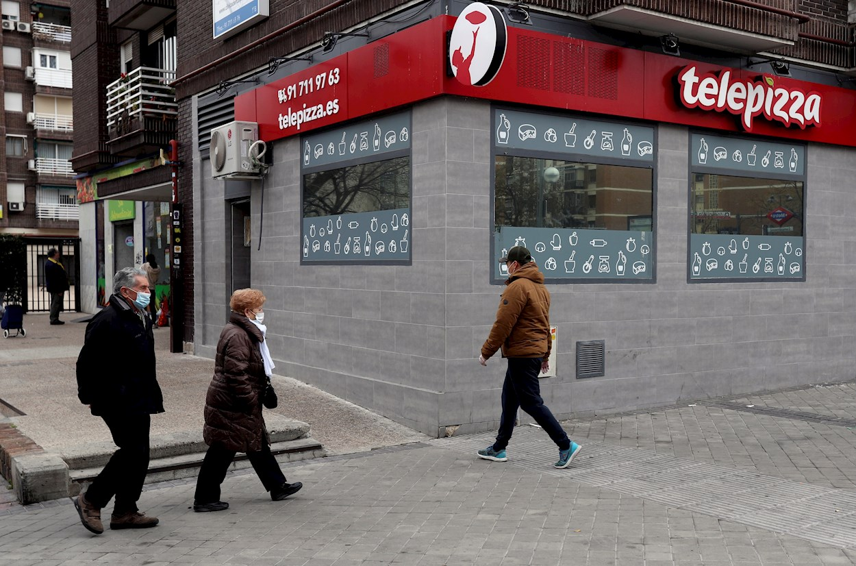 Peatones con mascarilla pasan frente a un restaurante Telepizza en Madrid. EFE/ Kiko Huesca