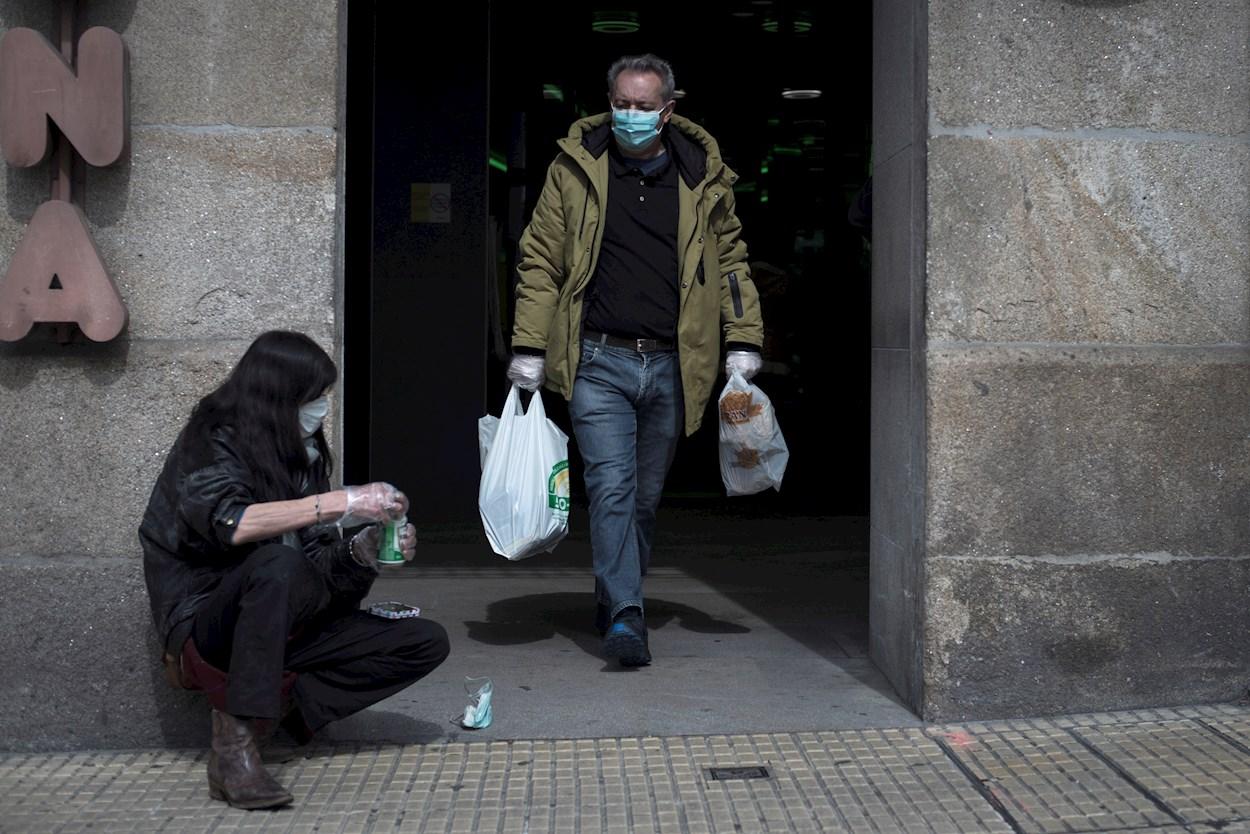 Un hombre pasa ante una mujer sin recursos a la salida de un supermercado en Ourense. EFE/Brais Lorenzo