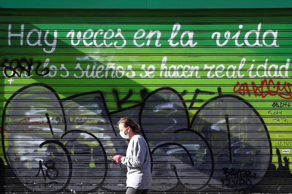Una mujer con marcarilla pasa por delante de un comercio cerrado en la madrileña calle de Alcalá. REUTERS/Sergio Perez