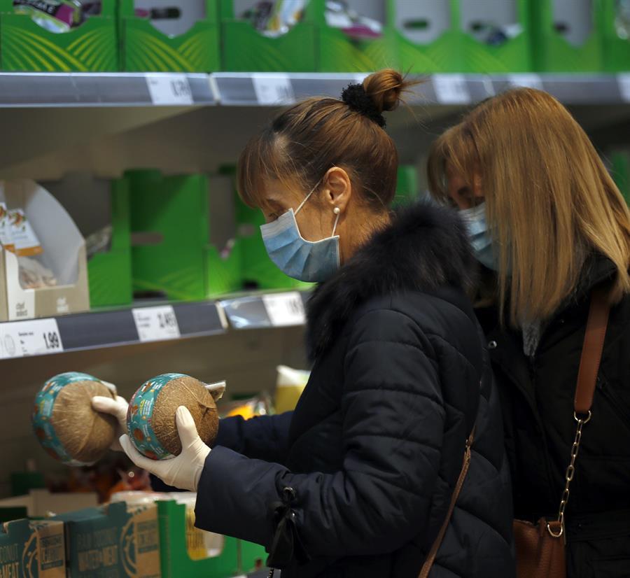 Dos mujeres con mascarilla y guantes se abastecen en un supermercado en Bilbao. EFE/LUIS TEJIDO