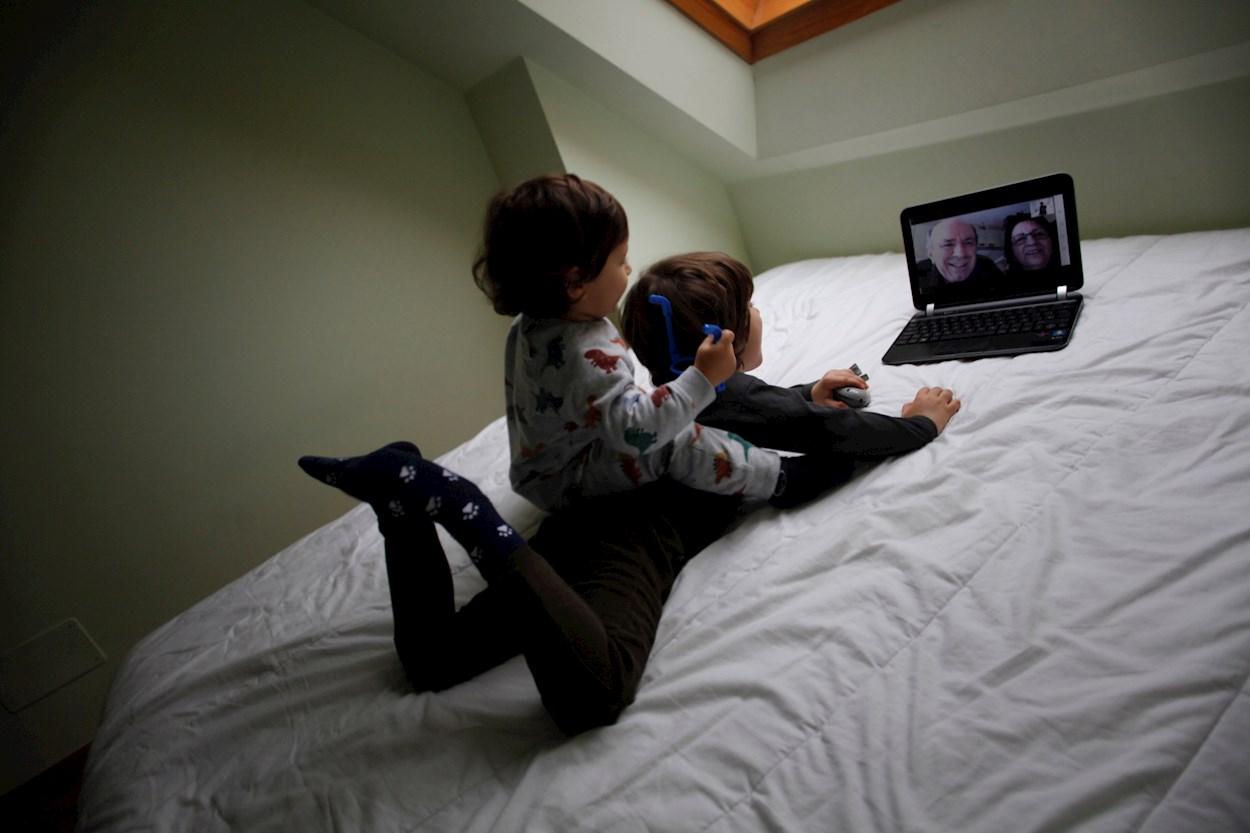 Dos niños conversan con sus abuelos mediante una videollamada en su casa. EFE/Cabalar