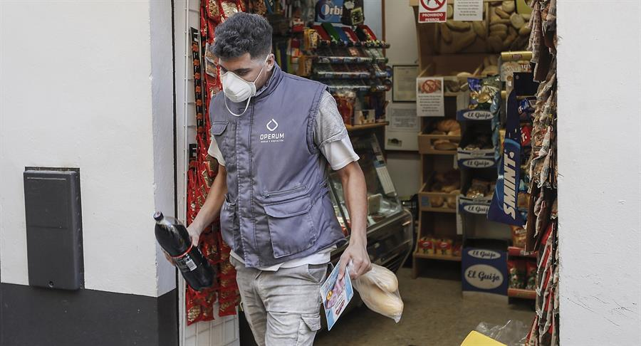 Un trabajador de una obra comprando en una tienda de alimentación de Sevilla en el primer día laborable tras la declaración de estado de alarma por la pandemia de coronavirus COVID-19. EFE/José Manuel Vidal