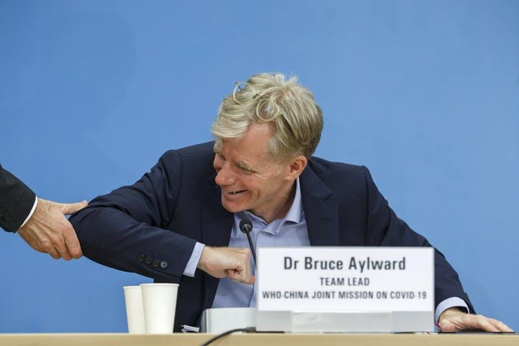 Bruce Aylward, líder de la coalición entre la OMS y China para luchar contra el COVID-19, ofrece el codo a un reportero que le extendía la mano. Salvatore di Nolfi/EPA-EFE
