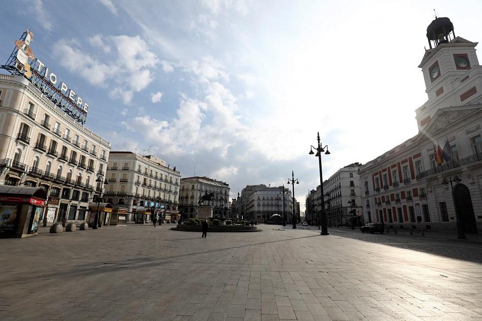Una mujer, con mascarilla, en una solitaria Puerta de Sol, la céntrica plaza de Madrid, el primer día de semiconfinamiento. REUTERS/Sergio Perez