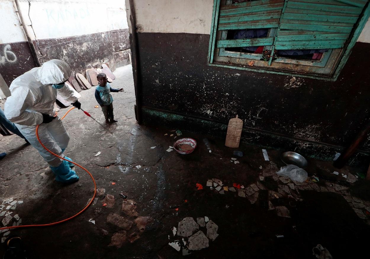 Un niño observa a un miembro de los servicios locales de higiene, con traje de protección y mascarilla, mientras desinfecta una escuela escuela coránica, en Dakar, Senegal. REUTERS / Zohra Bensemra