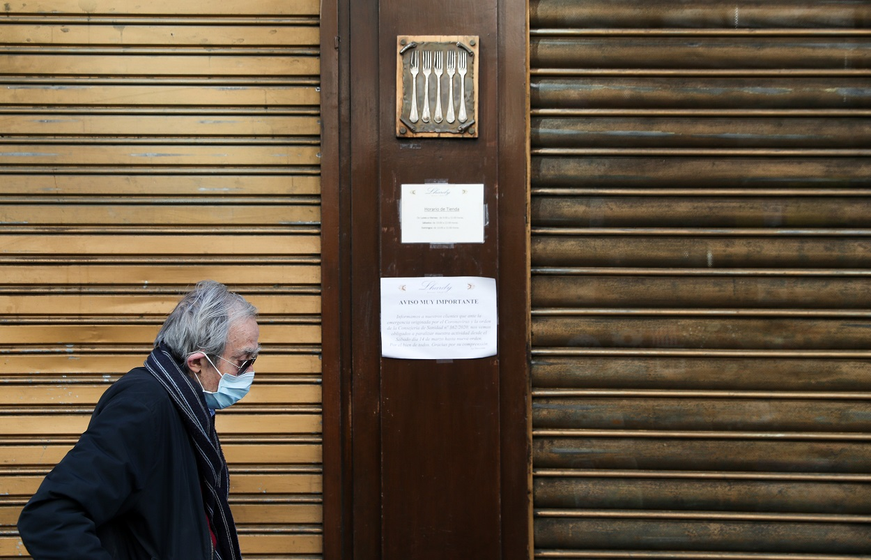 Un anciano con mascarilla pasa delante de un restaurante de cinco tenedores, en el centro de Madrid, cerrado por el estado de alarma por el coronavirus. REUTERS/Susana Vera