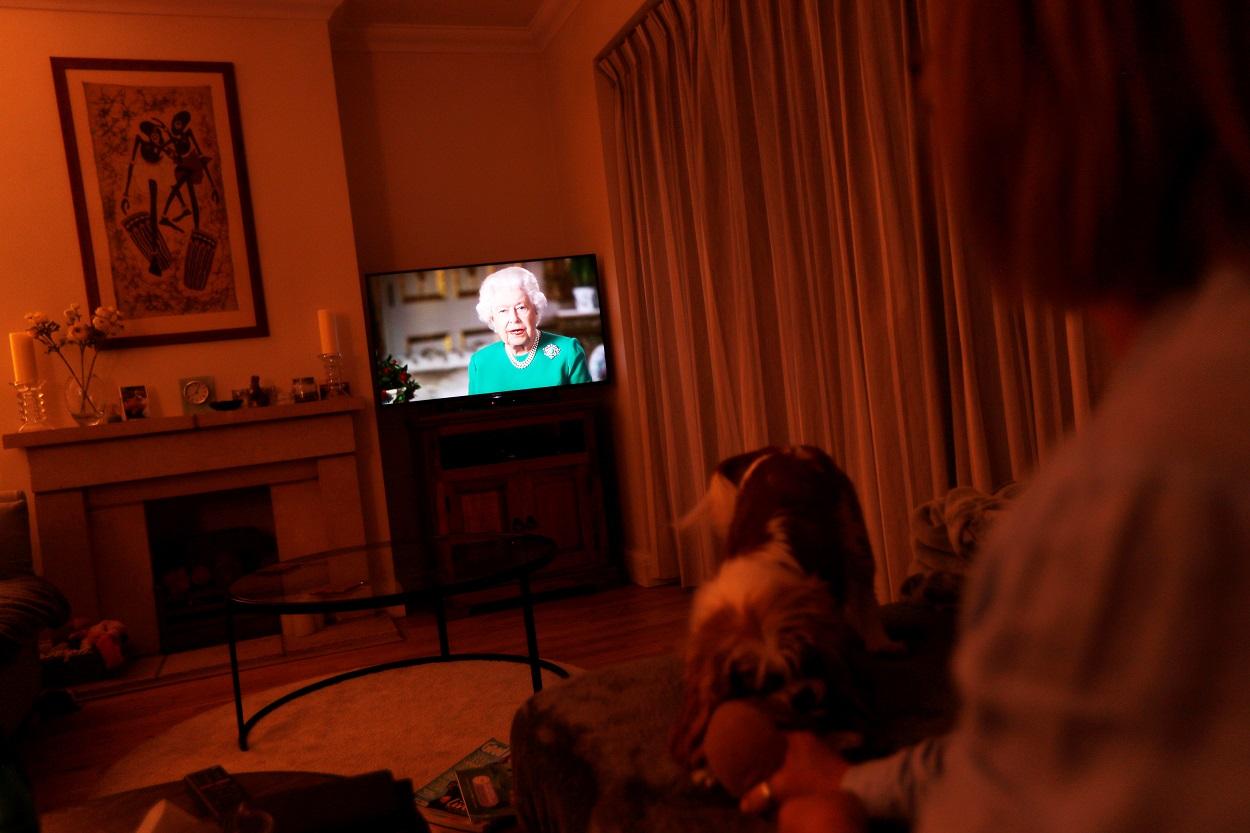 Una mujer atiende el mensaje televisado de la reina Isabel II, en su vivienda en la localidad británica de Weybridge. REUTERS/Peter Nicholls