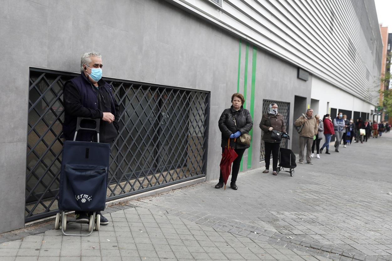 Varias personas hacen cola manteniendo la distancia social, esperando a entrar en un supermercado en Madrid. REUTERS/Sergio Perez
