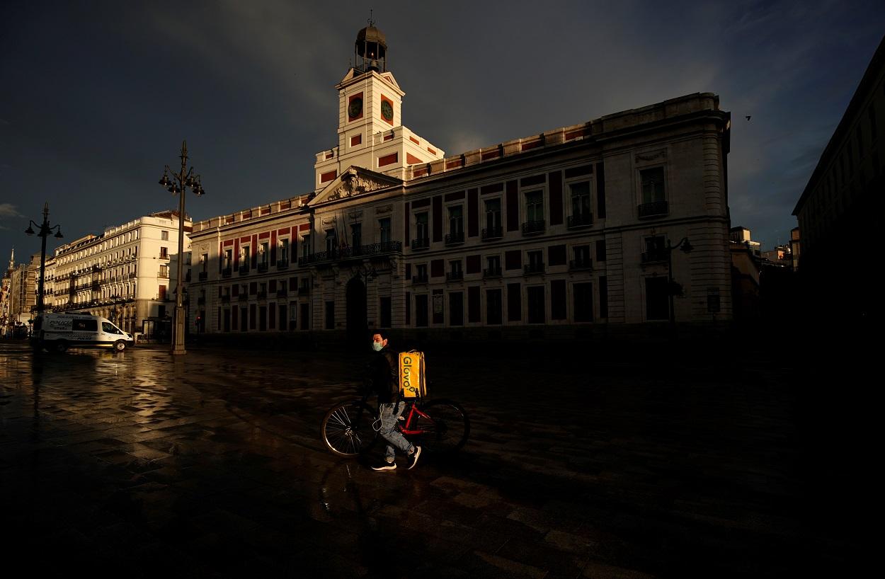 Un repartidor de Glovo con mascarilla pasa por una prácticamente desierta Puerta del Sol, de Madrid. REUTERS/Juan Medina