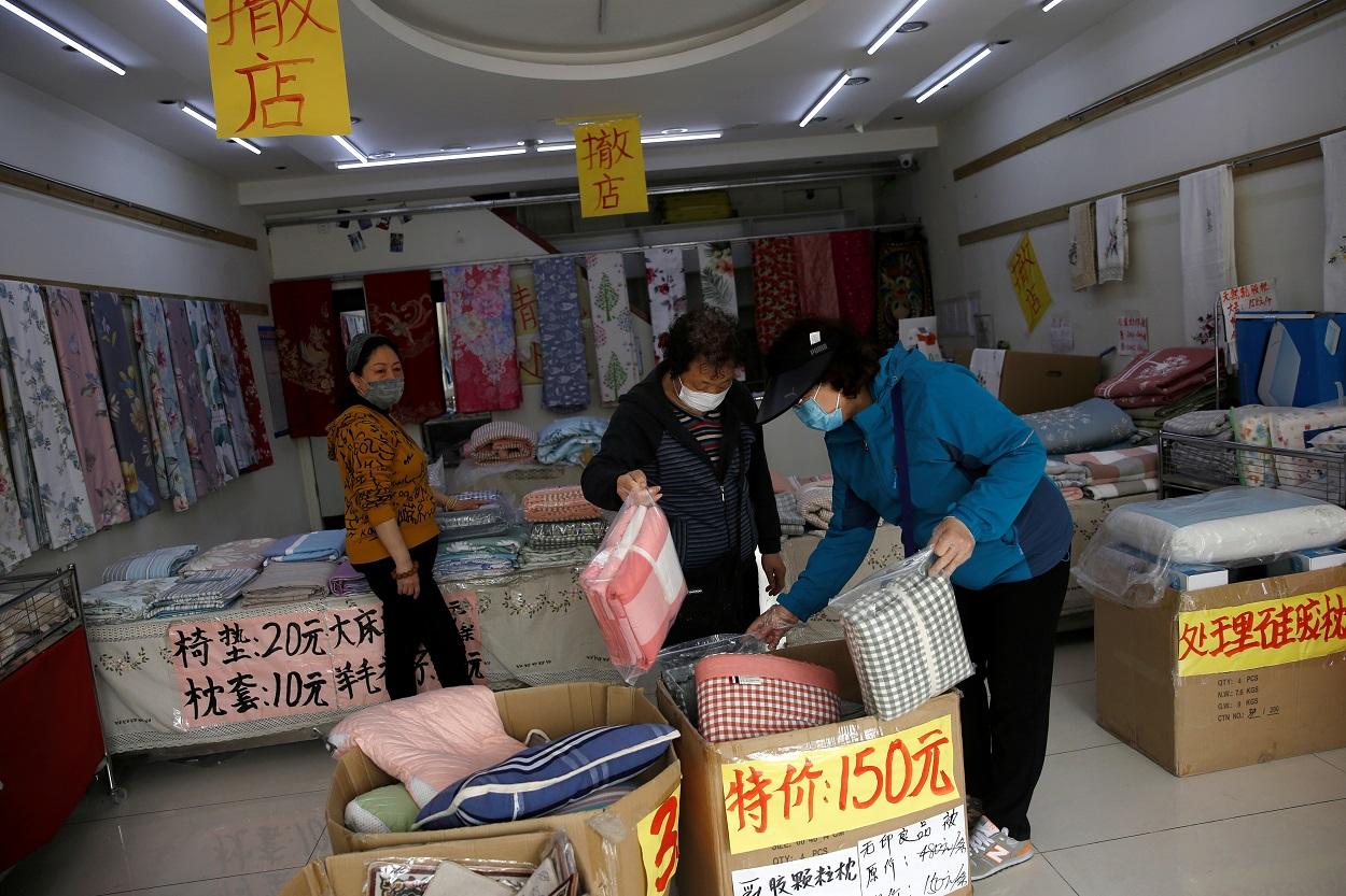 Unos clientes con mascarillas compran ropa de cama en una tienda de ropa para el hogar con avisos de liquidación, en Pekín.. REUTERS / Tingshu Wang