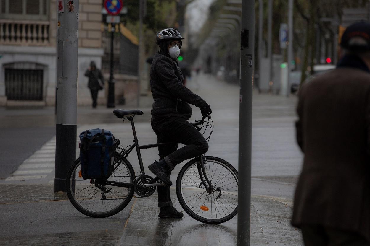 Una persona monta en bicicleta y se protege con una mascarilla en Barcelona. E.P./David Zorrakino