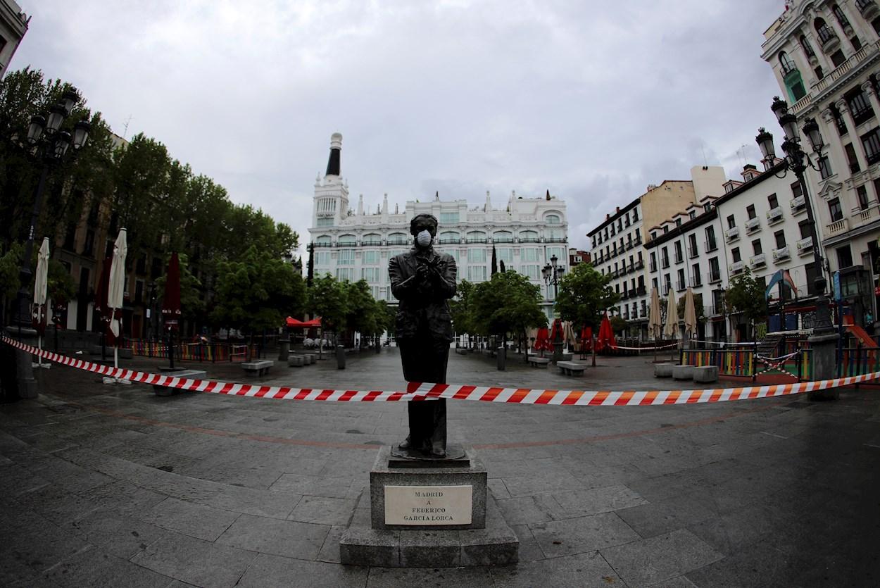 La estatua de Federico García Lorca situada en la madrileña plaza de Santa Ana, ataviada con una mascarilla facial. EFE/Rodrigo Jiménez