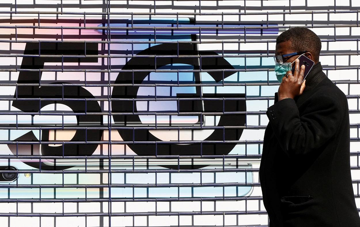 Un hombre con mascarilla hablando por su móvil, pasa delante del logo de la tecnología 5G, en una calle de Londres. REUTERS/John Sibley
