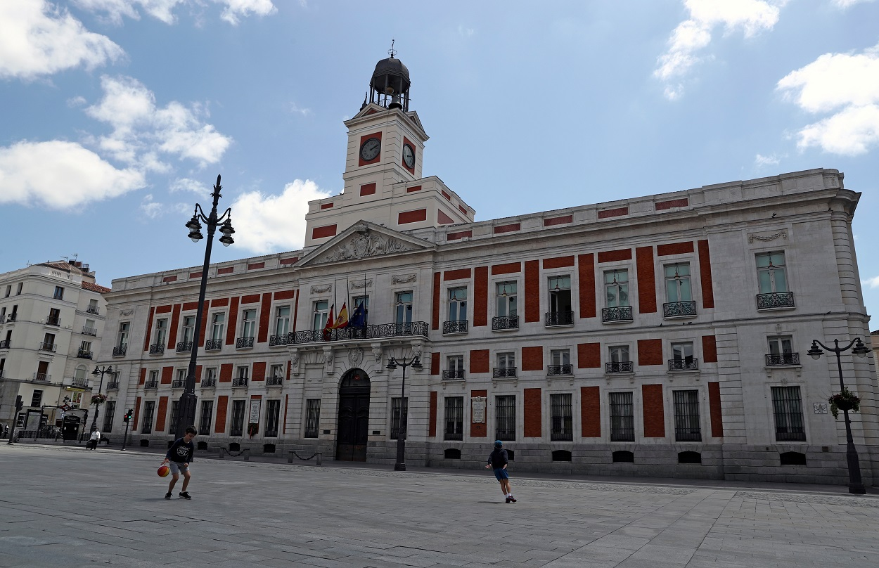 Dos niños juegan en la madrileña Puerta del Sol, frente al edificio de la Presidencia del gobierno autonómico. REUTERS/Sergio Perez