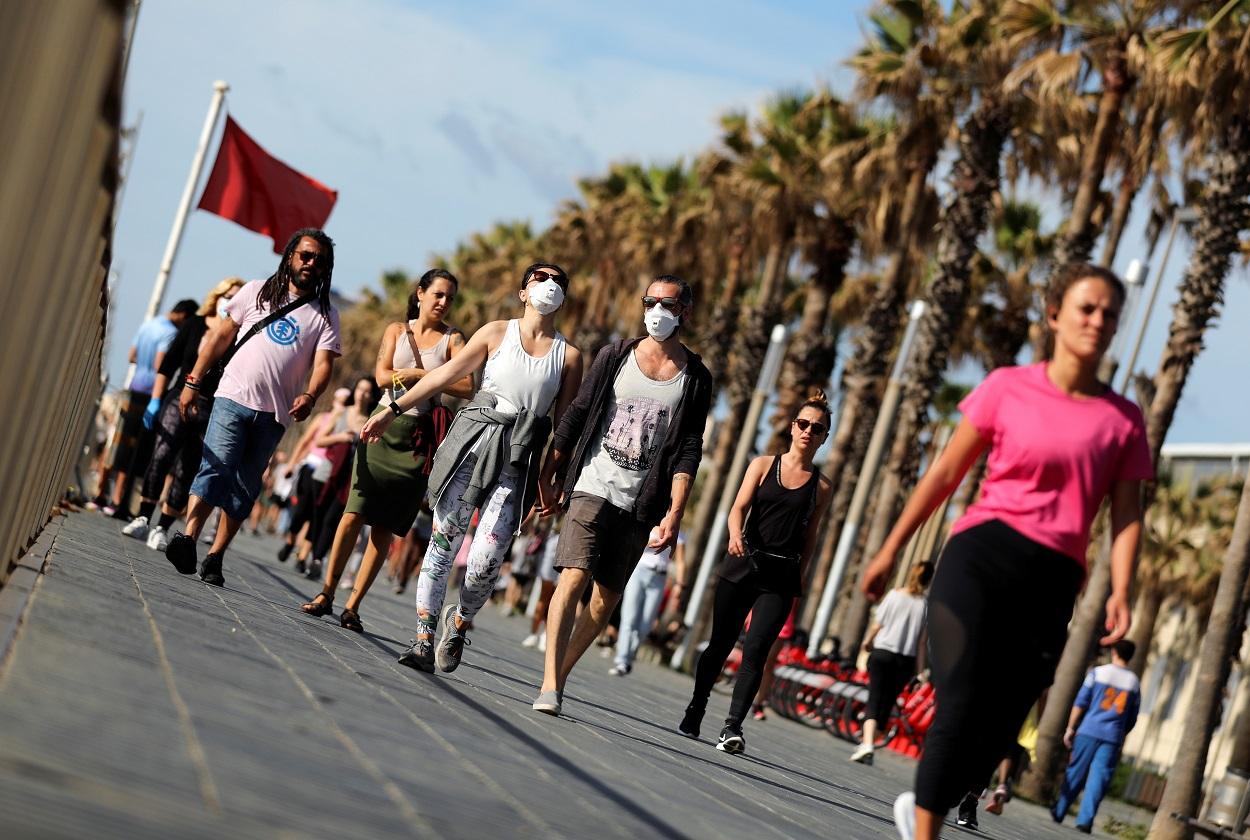 Personas paseando por la playa de la Barcelonetta, en el primer día que se permite paseos y actividades deportivas en la desescalada del estado de alarma por la pandemia de coronavirus. REUTERS/Nacho Doce